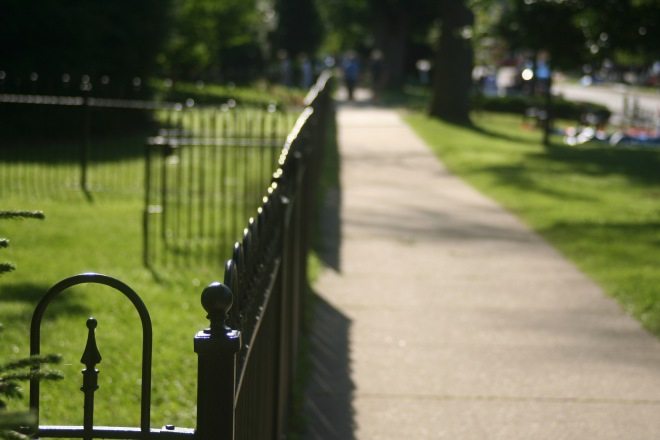 photo of an empty sidewalk and iron fence