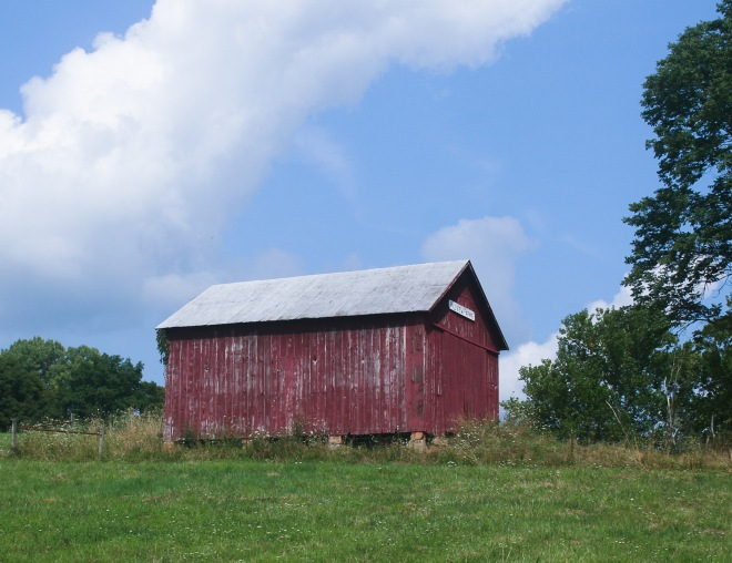 photo of a red barn on a hill