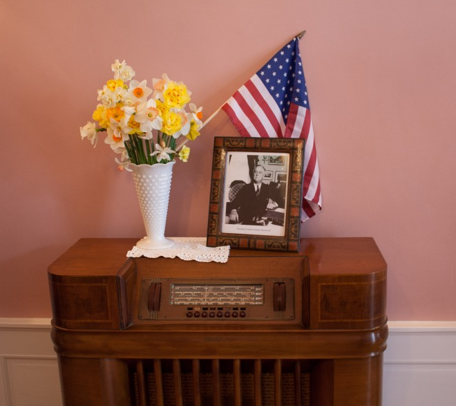 a 1940s floor radio with Roosevelt portrait and daffodils