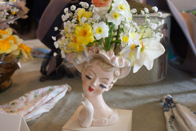 daffodils and baby's breath in a lady-head vase